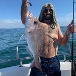Man showing fresh caught fish on Summer 2018-2019