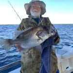 In Autumn 2019 Old Man holding a Fish on Fishing Charter