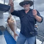 Old Man Showing a Fish on Fishing Charter