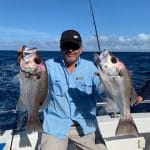 Old Man Showing two big Fishes on Fishing Charter