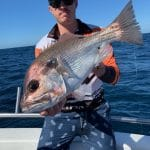 Man holding a Large Snapper Fish on Fishing Charter